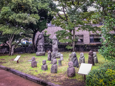 Group of Stone idols (Dolharubang, the grandfather stones) in Jeju Mokgwana, the oldest remaining building in Jeju for former central government office where the Joseon Period Magistrate of Jeju from 1392 to 1910