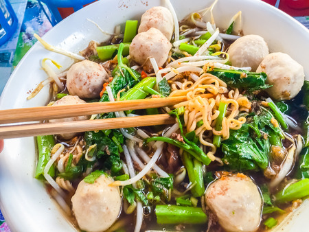 Popular street food in Thailand (Kuai Tiao Moo Namtok) that consisted of pork ball, pork meat, basil or thyme, bean sprouts, morning glory, noodle and creamy soup which favouring with sugar, fish sauce, chilli and vinegar marinade