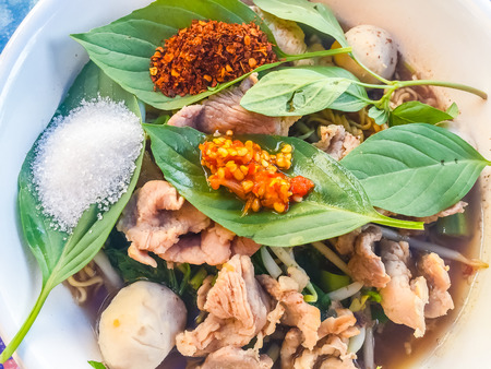 popular soup: Popular street food in Thailand, Spicy pork noodle that consisted of pork ball, pork meat, basil or thyme, bean sprouts, morning glory, noodle and creamy soup which favouring with sugar, fish sauce, chilli and vinegar marinade