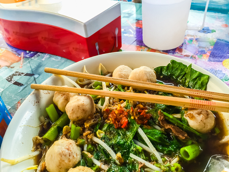 namtok: Popular street food in Thailand (Kuai Tiao Moo Namtok) that consisted of pork ball, pork meat, basil or thyme, bean sprouts, morning glory, noodle and creamy soup which favouring with sugar, fish sauce, chilli and vinegar marinade