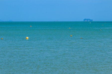 Yellow Mooring buoys balls are floating in the blue sea with island and blue sky background.