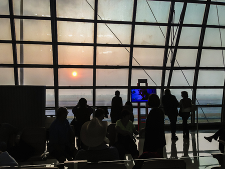 Tourists waiting for morning flight at the airport gate and they looking through the window glass to see the beautiful of sunrise. Sunshine in the morning keep back light and silhouettes of travelers Editöryel