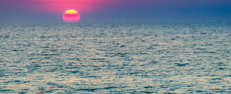 outflow: Beautiful sunset over the sea, view from the beach. Round and bright sun in dusk over calm sea  with blurred dramatic sky background.