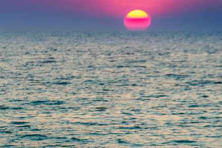 Beautiful sunset over the sea, view from the beach. Round and bright sun in dusk over calm sea  with blurred dramatic sky background.