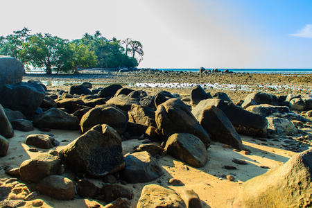 Beautiful rock stones on the beach when the sea water receded with dramatic blue sky background on the cloudy day.