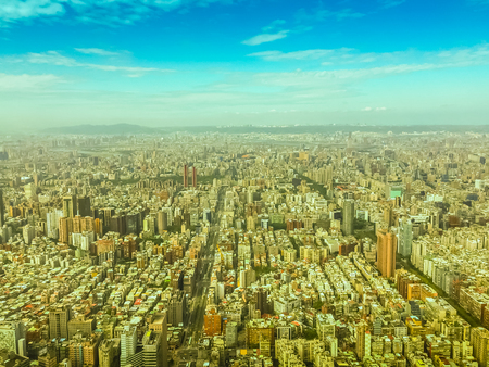 overpopulated: Aerial panorama over Taipei, capital City of Taiwan, on a blue sky and cloudy day