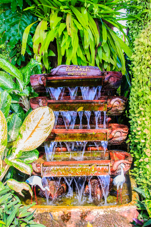 peace pipe: Small waterfall garden decoration at the front of the office with welcome signboard Stock Photo