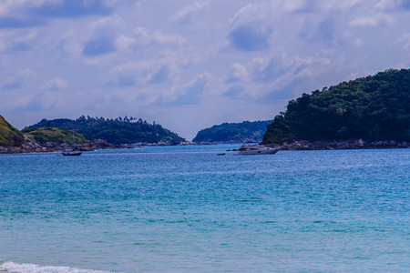 Beautiful seascape view of Nai Harn Beach Phuket with sail yachts, catamarans and islands on background