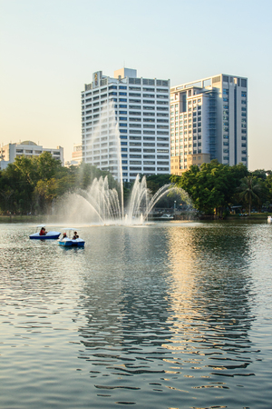 Beautiful fountains in the lake at Lumpini Park, Bangkok Thailand. Tranquil public park garden with pond, fountain, and boats in the middle of the city for people on holiday or after work leisured.