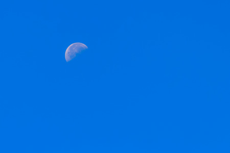 waxing gibbous: Half Moon During Day in Blue Sky. Bright moon orbiting earth in a blue clear sky during the daytime showing craters. Waxing Gibbous past first quarter. Southern hemisphere, winter.