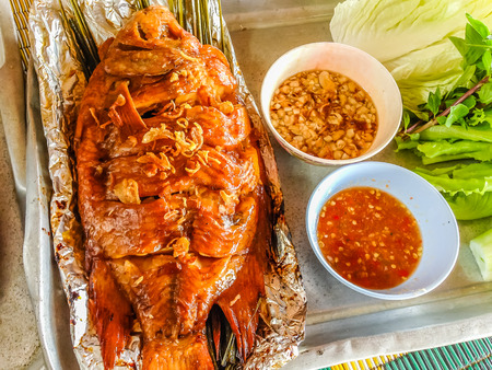 Red talapia fish grilled with herb in aluminium foil that ready to eat by put the fish wrapped in vetgetable leaves and then dipped in a sweet or hot sauce. Stock Photo