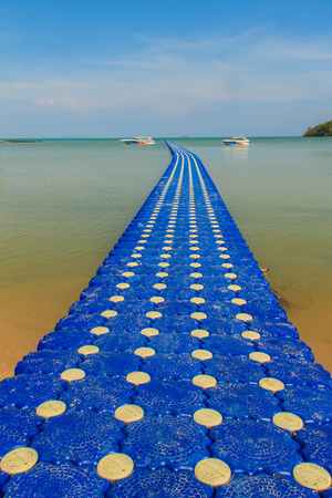 Beautiful blue pontoon made from plastic floating in the sea, rotomolding jetty, a landing stage or small pier at which boats can dock or be moored, floating pier