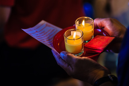 richness: Poor light with noise grain of hand holding candles in the transparent glasses shining in the darkness as a symbol of contemplation, meditation and calmness. People praying for good luck and richness.