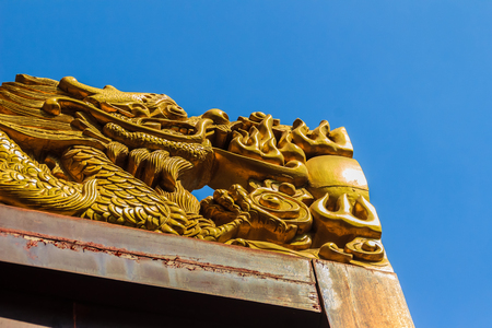 Beautiful Craved Golden dragon on top of the wooden door at Chinese temple