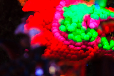 Chinese New Year Dragon Lights with Bokeh Background. Closeup of colorful dragon on night black background (soft blur with poor light and noise grain) during Chinese New Year festival. Stock Photo