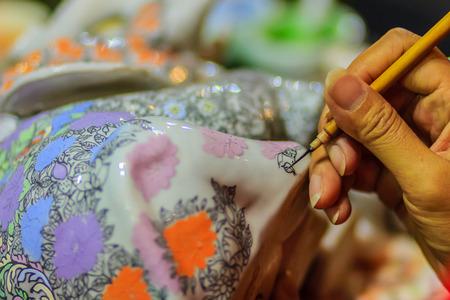 有名なタイ 5 色磁器陶磁器ベンジャロン パターンの傑作絵画中にタイの女性アーティストの手を閉じます。 写真素材