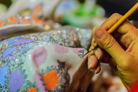 Close up hand of Thai woman artist during painting the masterpiece of Benjarong patterns, the famous thai 5- colored porcelain ceramic wares.