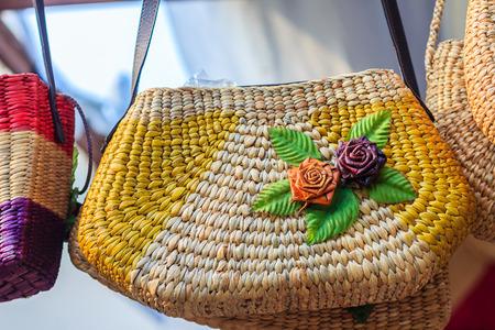 Beautiful rose flowers pattern on on handbag weaving, made from Water Hyacinth haulm. Dried water hyacinth lady handbag for sale in walking street market in Bangkok, Thailand. Stock Photo