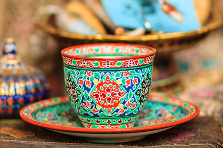 Vintage Thais style porcelain coffee cup handmade. Beautiful traditional Thai five-colored porcelain ceramic coffee cup. Benjarong Porcelain coffee cup for sale in the flea market, Thailand. Stock Photo
