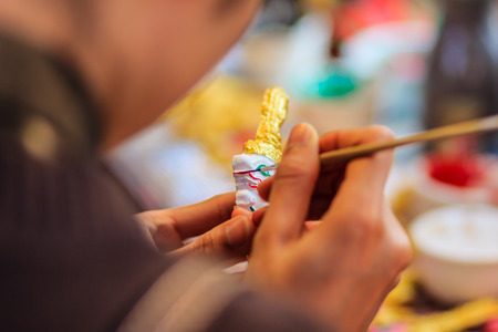 Close up hand of Thai sculptor during painting the masterpiece of puppet patterns,