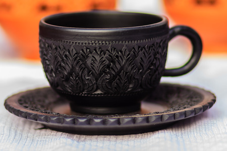 Beautiful Black Vintage Thais style porcelain teacup, coffee cup hand made. Set of Black coffee cup with black plate in Thais style pattern carving. Stock Photo