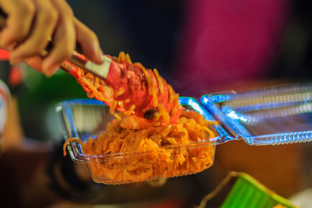 Close up hand of vendor during cooking for the original Thai Fried Noodle, stir-fried noodle with shrimp and egg commonly served as a street food popular in Thailand