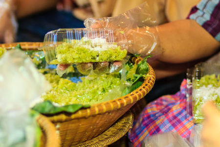 Thai vendor is selling shredded rice grain dessert to the customer at night market. Steamed shredded rice grain with coconut, This Thai desert is called  Khao Mao .