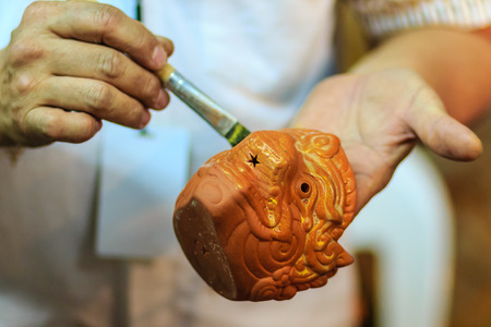 Close up hand of Thai sculptor during painting the masterpiece of hanuman puppet doll at night market