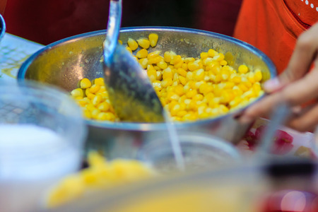 Close up hand of street vendor during cooking for mixed corn butter, sweet and simply Thai dessert.