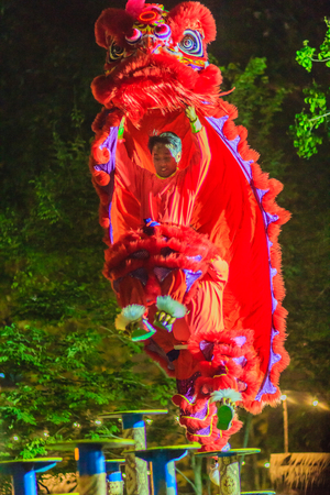 Bangkok, Thailand - January 29, 2017: Unidentified lion dance team are awesome dancing show on the pole at night during Chinese new year festival in Bangkok, Thailand. Shot with grain and blurred