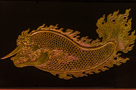 Beautiful glass ornament with gold filigree of golden fish with horn and fang