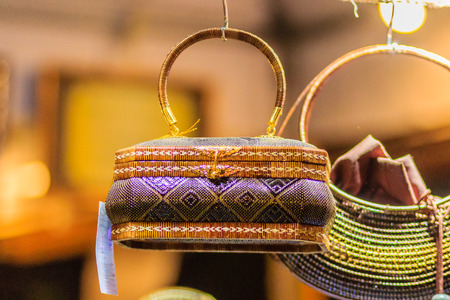 basketry: Beautiful lady handbags and basketry that made from Lygodium (climbing fern), or Yan lipao in Thai, the famous product from Southern Thailand for sale at night market, Bangkok. Night shot with grain