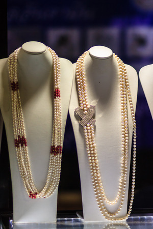 Beautiful long pearl necklaces are displayed at a jewelry shop. Poor light with noise grain shot Stock Photo
