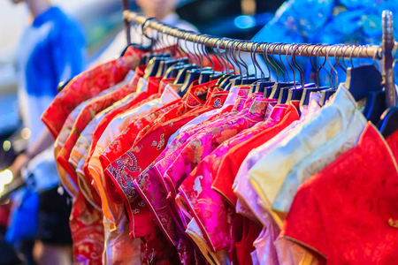 Beautiful Qipao (cheongsam dress or Chinese dress) for women hanging on a clothes line in night market for sale to customers during the festival is Chinese New Year at Bangkok, Thailand. Stock Photo