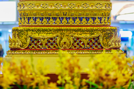 Beautiful golden base of the movable throne in Thais style patterns for contain the Lord Buddha relics enshrined. Located at the departure floor of Suvarnabhumi airport, Bangkok, Thailand.
