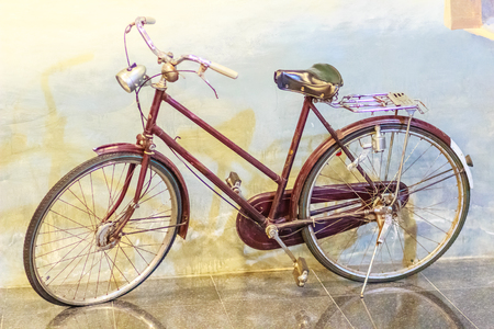 Vintage bicycle leaning to the wall. Old rusty bicycle in the country. Antique bike collection in the museum.