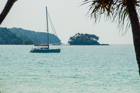Keel boat moored at shore side, view from forest beach. Seascape view with forest tree and sailboat. Peaceful beach with yacht and tree. Sailboat or keel boat in the tree frame at Naiyang beach Phuket