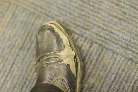 Close-up view of wear and tear office mans black leather shoes. Old wear and tear black shoe on floor background, abstract old time, jobless and work hard concept.