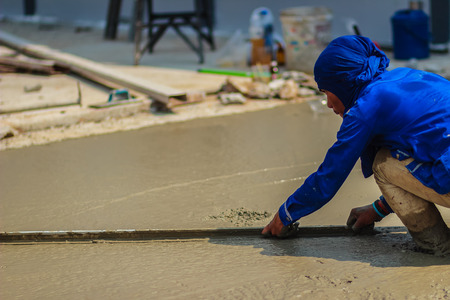 concrete surface finishing: Masonry worker is using long trowel to smooth or leveling concrete flooring work step of the building construction. Stock Photo