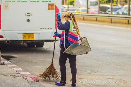 Bangkok, Thailand - February 21, 2017: View of Bangkok municipal staff sweeping the garbage on the street. Road sweeper worker cleaning city street with broom tool