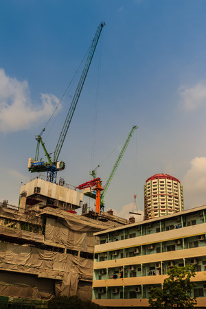View of luffing jib tower crane at condominium construction site over steel framework among high rise buildings in the center of Bangkok, Thailand. Stock Photo