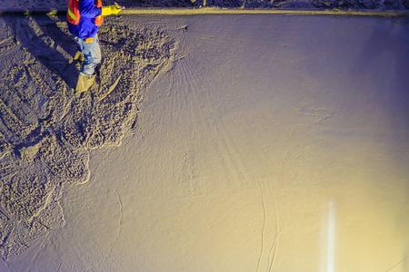 Mason-arbeider die beton met troffels nivelleren, metselaarhanden die gegoten beton uitspreiden. Betonnerende werknemers egaliseren gestort vloeibaar beton op een stalen wapening om een ??sterke vloerplaat te vormen.