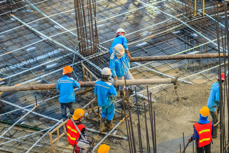 concreting: Construction workers are pouring concrete in post-tension flooring work. Mason workers carrying hose from concrete pump or also known as elephant hose during concreting work at construction site