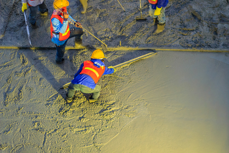 concreting: Mason worker leveling concrete with trowels, mason hands spreading poured concrete. Concreting workers are leveling poured liquid concrete on a steel reinforcement to form strong floor slab. Stock Photo