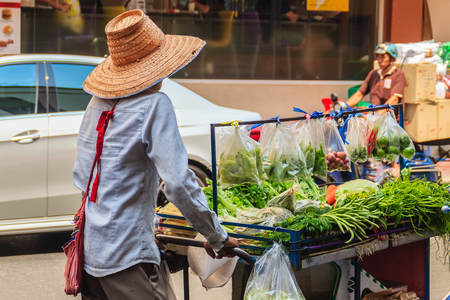 Bangkok, Thailand - March 2, 2017: A vegetable vendor pushing a cart filled with local vegetables for sale in the streets of Bangkok, Thailand. Editoriali