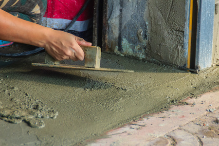 concreting: Mason worker use trowel to smooth or leveling liquid concrete of flooring work in step of the building improvement.