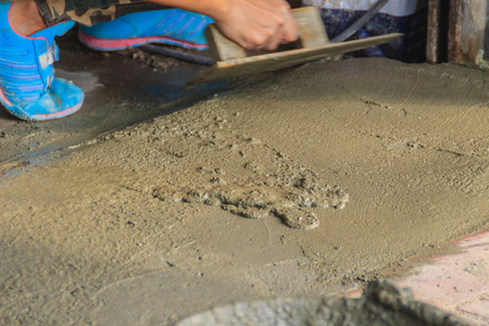 Mason worker use trowel to smooth or leveling liquid concrete of flooring work in step of the building improvement.