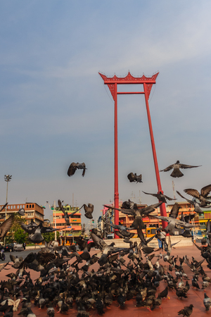 Red giant swing or Sao Ching Cha with the crowd of pigeon, one of the most famous tourist attraction and landmark in Bangkok, Thailand.