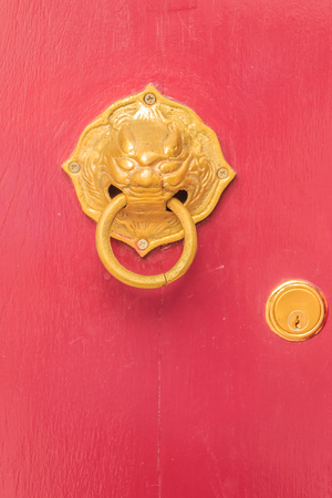 Golden door knocker in the shape of lion with ring on a red wooden door. Close up wooden Chinese style red door with lion head doorknob. Stock Photo