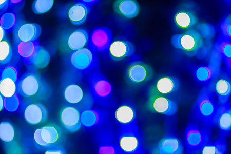 Beautiful blue bokeh abstract light background. Wonderful Defocused abstract blue christmas background. Abstract christmas lights as background in the night with noise grain and poor light. Stock Photo